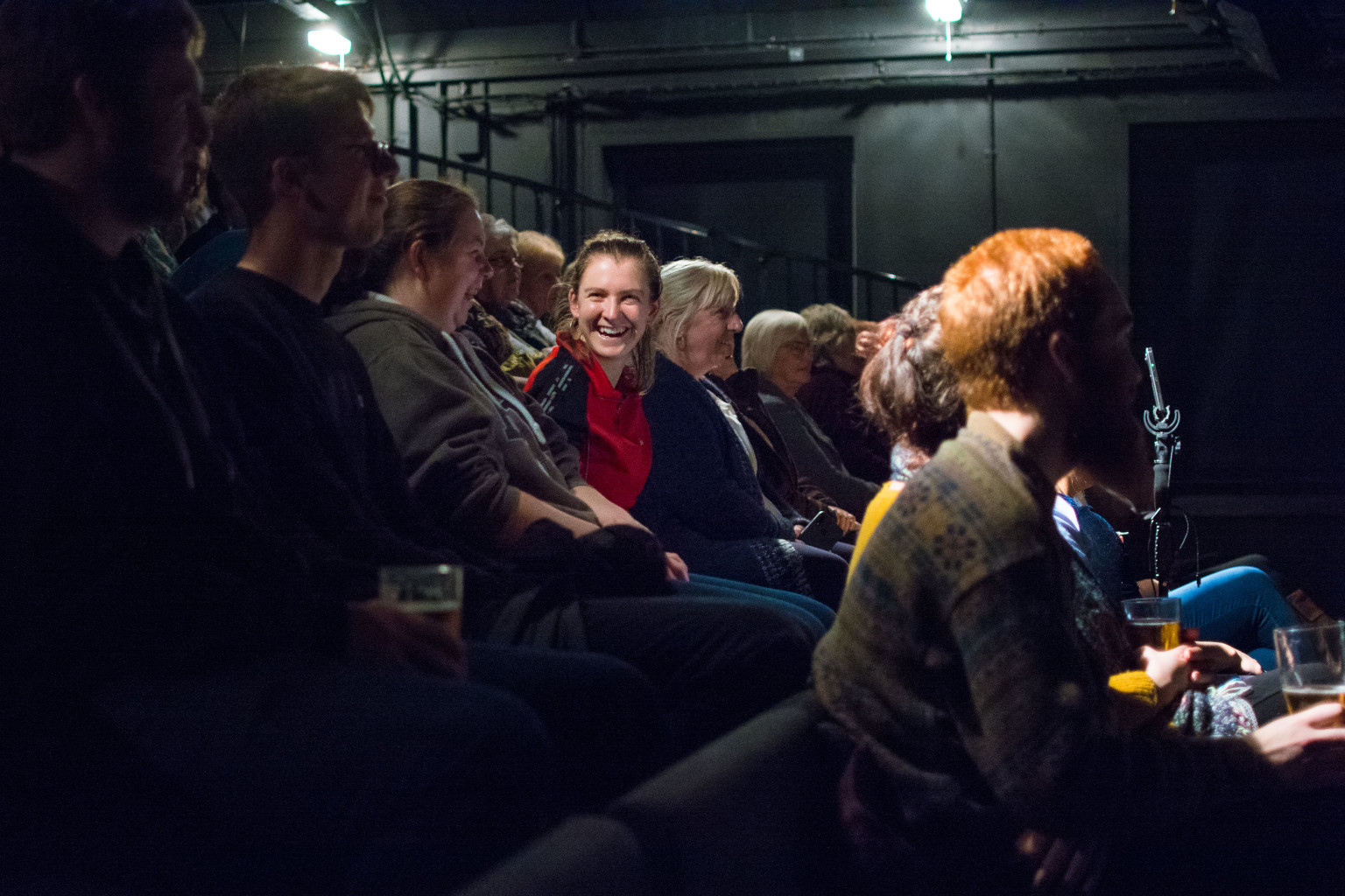 An audience in a dark studio space, one person grinning is spotlighted in the centre of the photograph