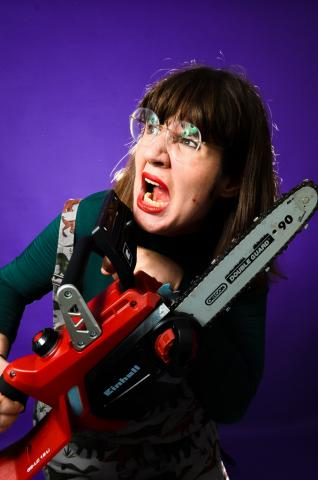 Rebekka weilding a chainsaw